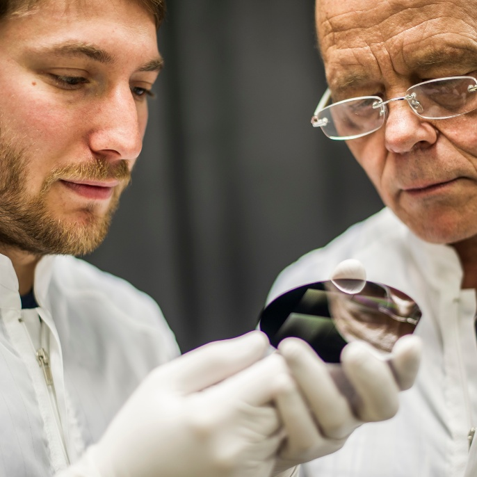 Young scientist at the Stuttgart Research Center of Photonic Engineering demonstrating a developed product to a senior researcher