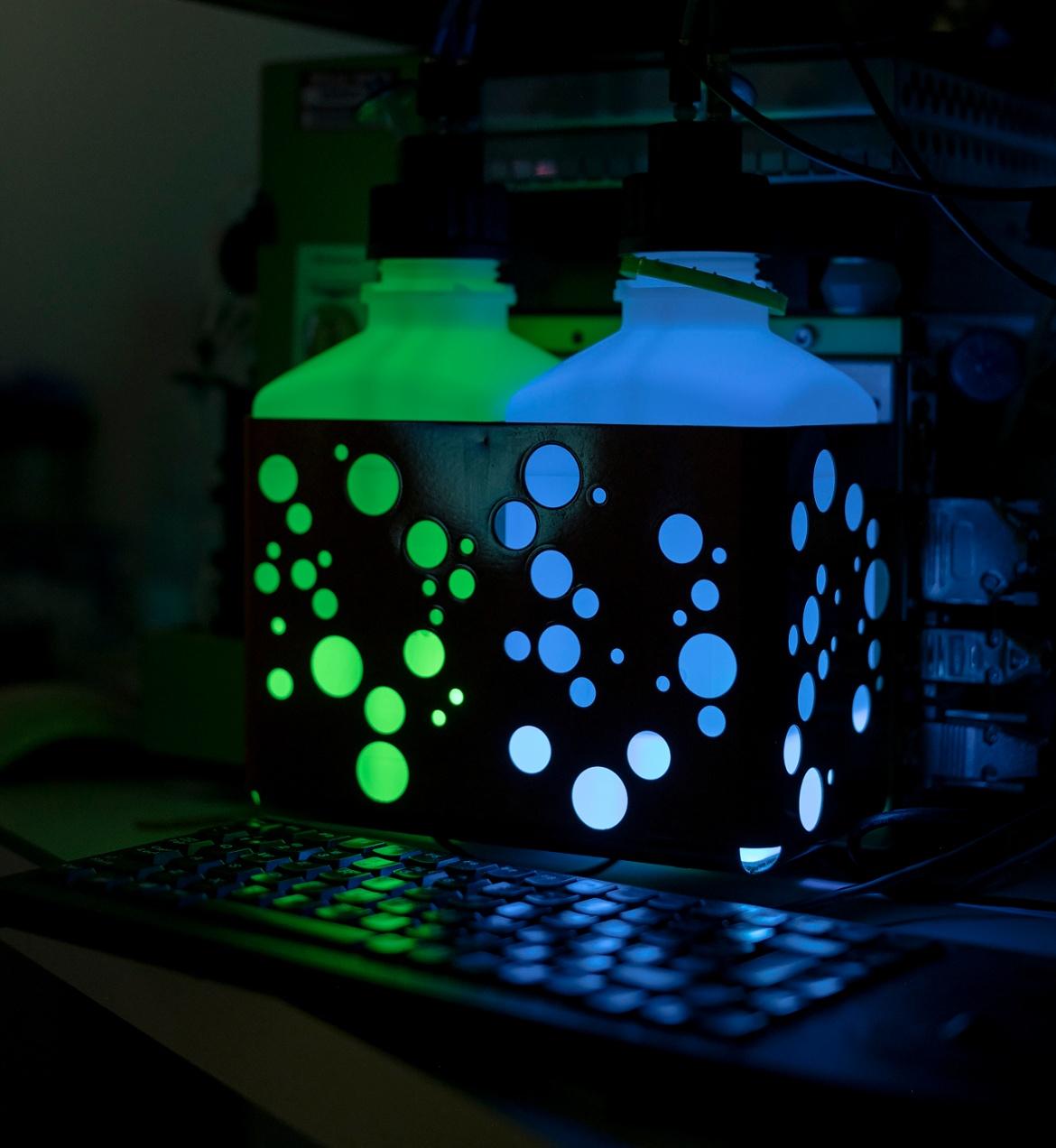 Gefäße die in einem dunkklen Labor die grün und blau leuchten.