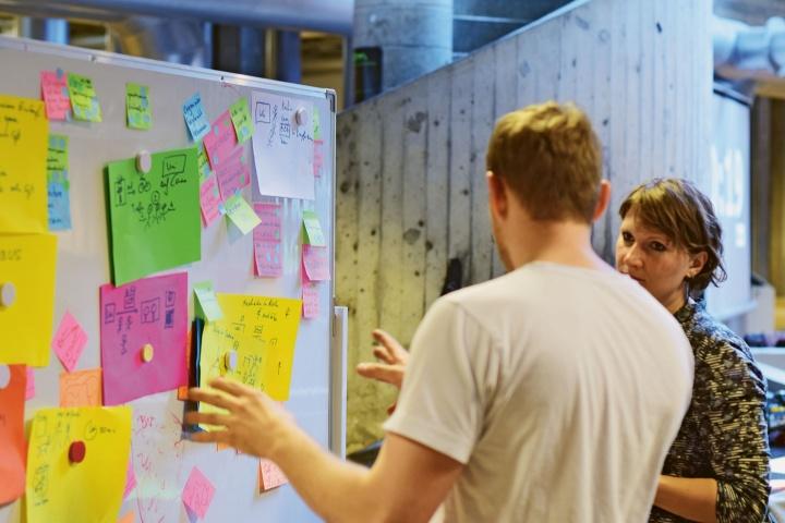 Workshop Teilnehmende vor einer Pinnwand.