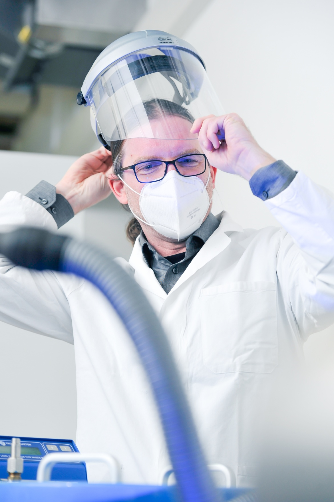 Prof. Markus Morrison puts on a face shield in the lab.