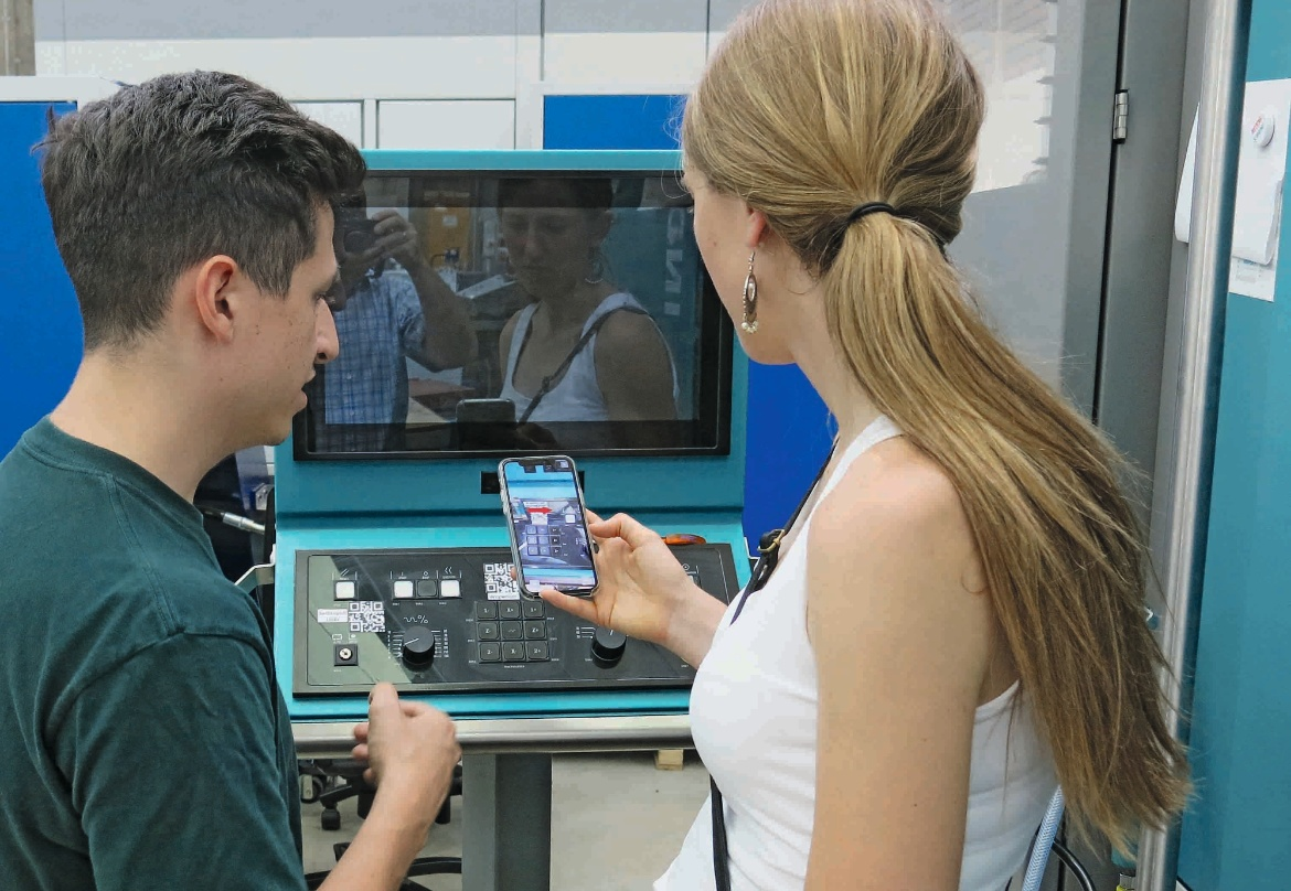 A young woman and a young man test the augmented reality app on the screen