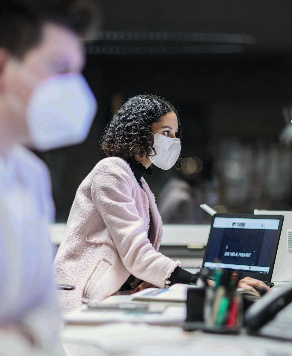 Zwei Personen arbeiten an Laptops.