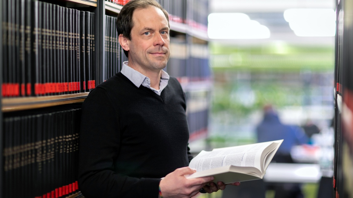 Prof. Dr. Syn Schmitt in the library holding a book (c) University of Stuttgart/U. Regenscheit