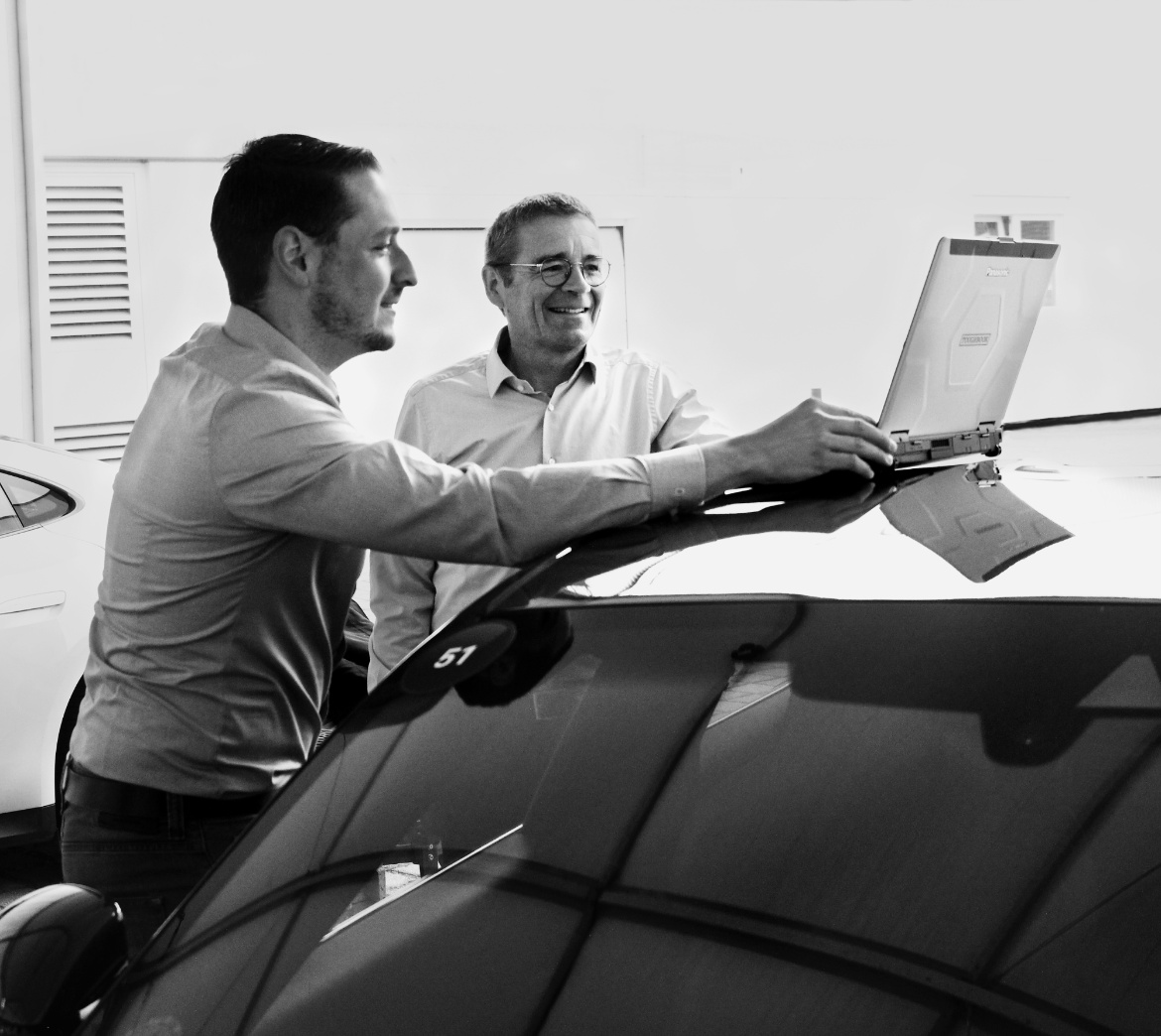 Peter Schäfer and another man are looking at a laptop standing on the roof of a car.