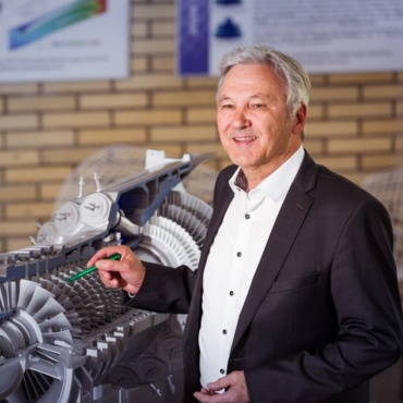 Prof. Schmauder stands next to a gas turbine model