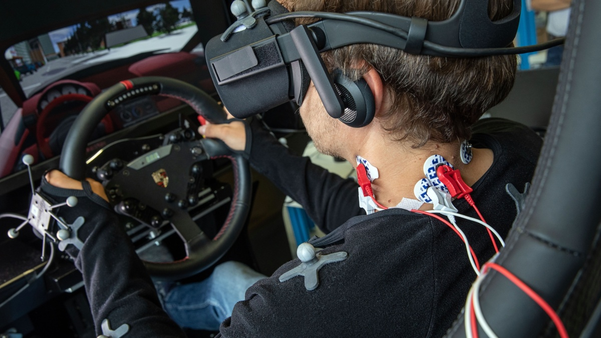 Detailed view of the wires attached to the neck of the man in the driving simulator.