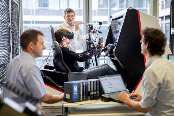 Ein Mann sitzt im Fahrsimulator. Hinter ihm steht Prof. Jörg Fehr. Im Vordergrund sitzen zwei Kollegen.