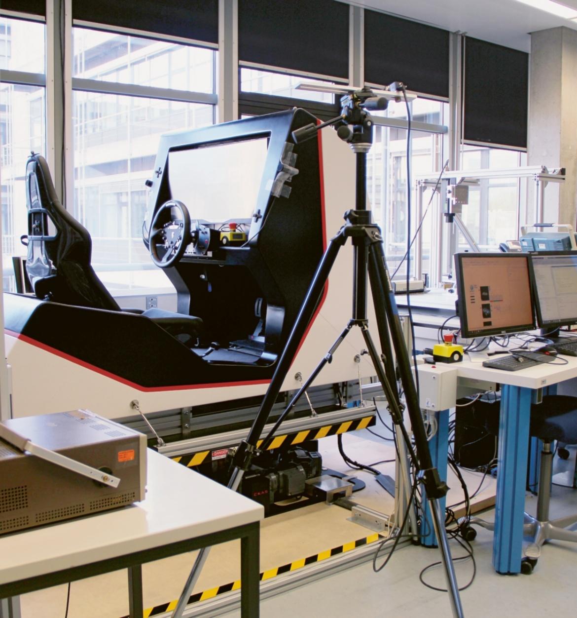 Der Fahrsimulator hat einen Schalensitz, ein Lenkrad und einen Bildschirm. Zudem gibt es eine Kamera und mehrere Kabel zum Messen der Muskelanspannung.
