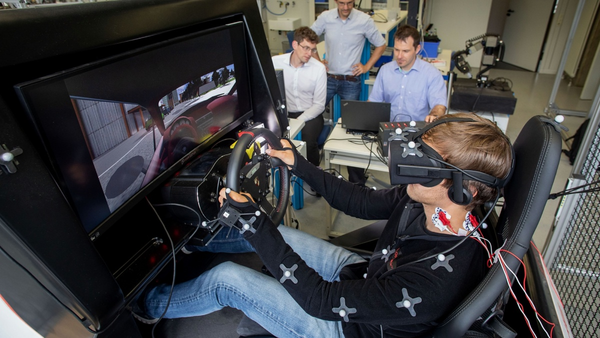 A man sits on a body-contoured seat wearing VR glasses and steers using a steering wheel. His neck and arm are wired to measure the muscle tension.
