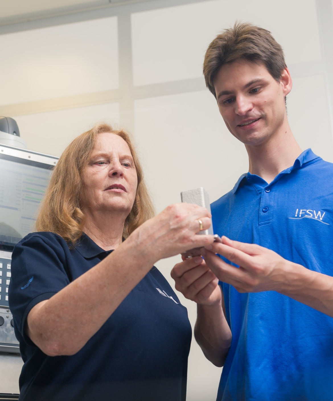 Dr. Becker (left) and Steffen Boley (right) together hold a test component in their hands and look at it while testing.