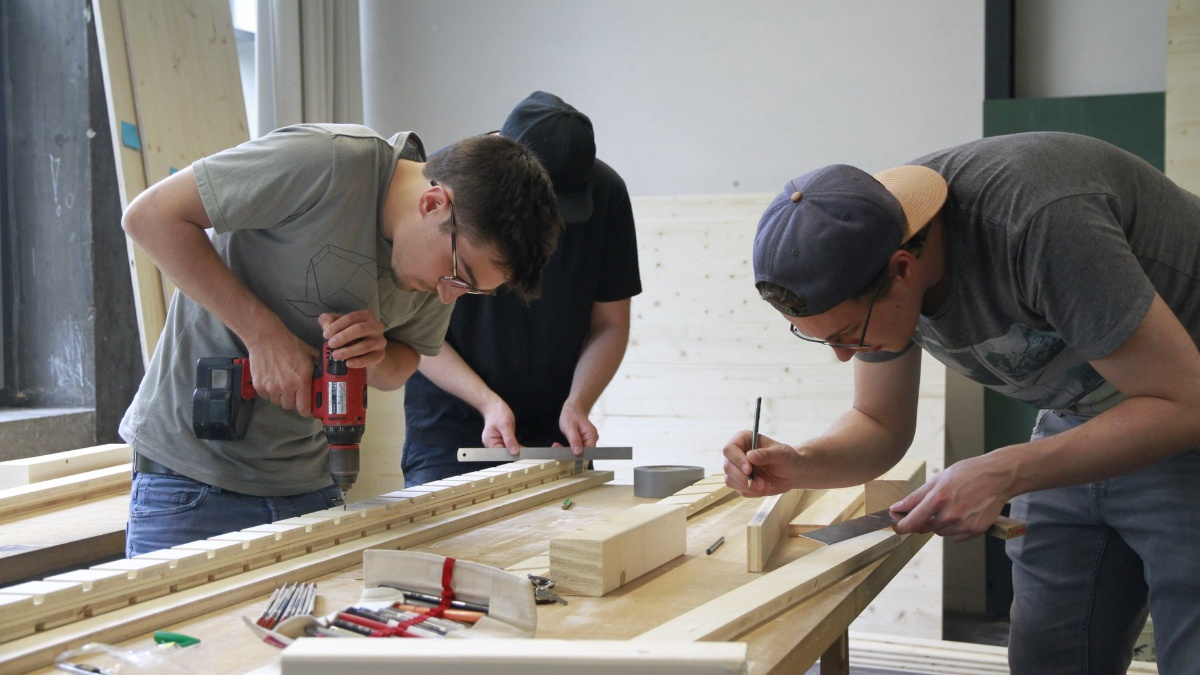 Three students work with wood at a work table. One holds a drill in his hand, one a ruler and one a pencil.