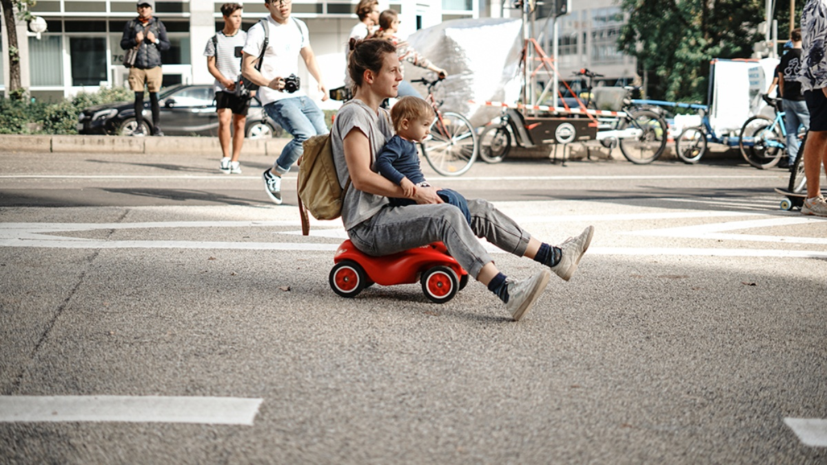 Adult with child on lap rolls across the street in a bobycar