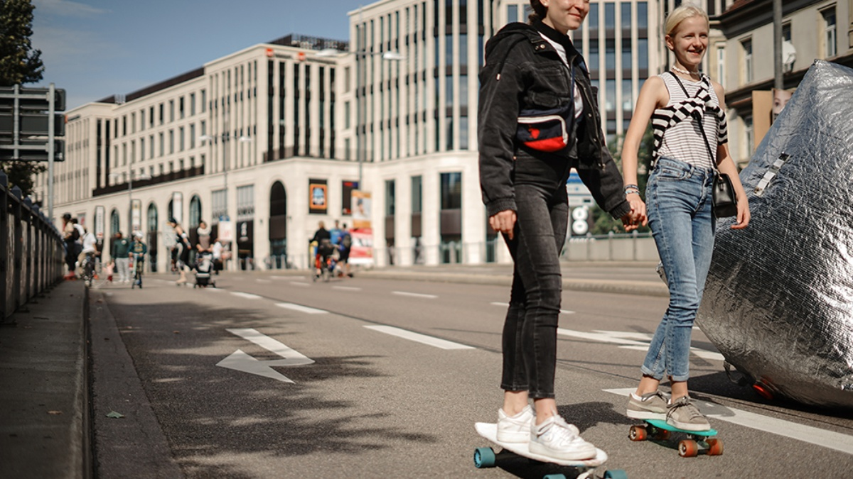Two female teenagers ride hand in hand with a skateboard across the street