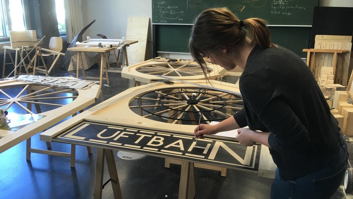 Studentin gestaltet mit einem Pinsel den Schriftzug
