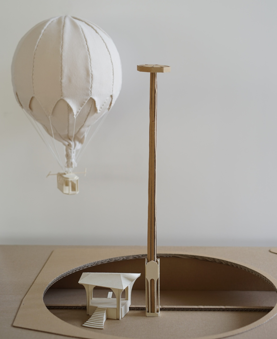 Model made of fabric and cardboard showing the hot air balloon with gondola, suspended from a vertical pole device.