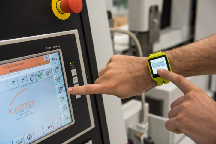 A smartwatch tells the machine operator when it is time to insert a component or to remove a finished part. (c) Universität Stuttgart/Max Kovalenko