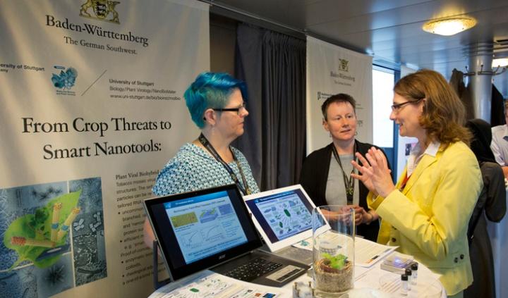 Sabine Eiben (links) und Christina Wege (Mitte) präsentieren ihre Forschungsarbeit im Rahmen der Nobelpreisträgertagung. (c) Staatsministerium Baden-Württemberg / Uli Regenscheit