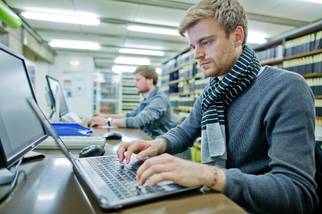 Das Bild zeigt einen jungen Mann, der vor einem Laptop sitzt.