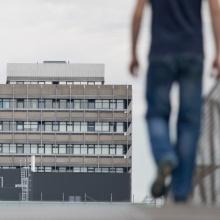 Das Bild zeigt einen Mann, wie er in Richtung eines Unigebäudes läuft
