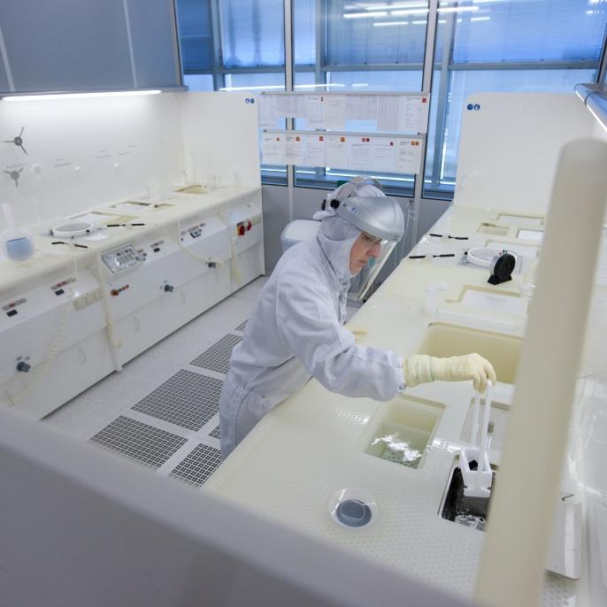 Forscher bei der Bearbeitung eines Wafers in einem Reinraum