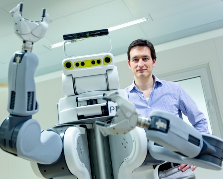 Prof. Marc Toussaint with his robot that is capable of learning. (c)