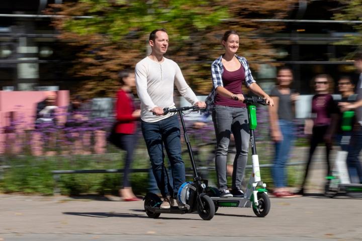 Studierende fahren mit einem E-Scooter.