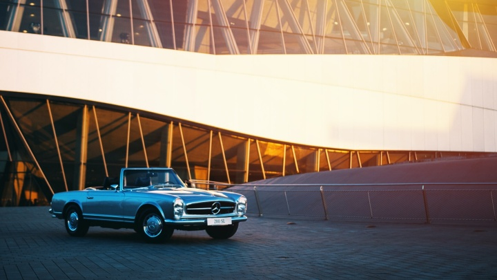 A Mercedes stands in front of a modern building