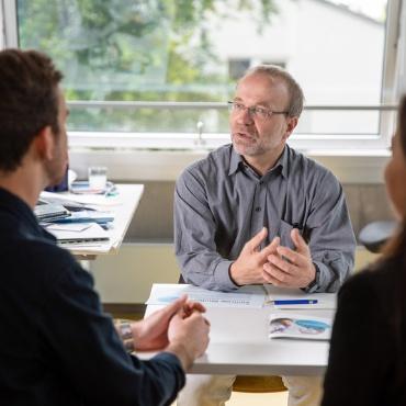 Ein Studienberater und zwei Ratsuchende in der Zentralen Studienberatung der Universität Stuttgart.