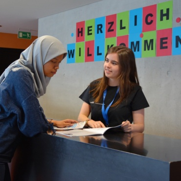 A foreign student is adviced by another student in the International Office of the University of Stuttgart.