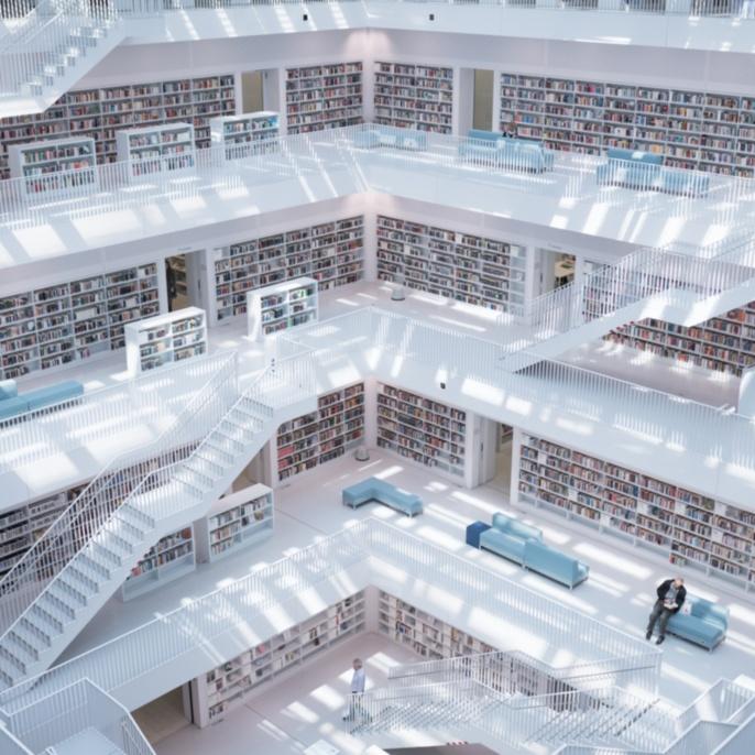 Die moderne Stadtbibliothek in Stuttgart ist in einem Quader mit vielen Weißflächen im Innenraum untergebracht.