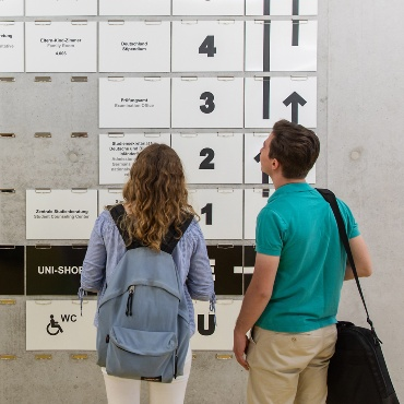 Students looking on the signboard of the house of students of the University of Stuttgart.