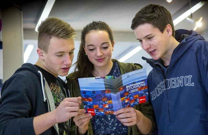 Schülerinnen und Schüler lesen gemeinsam einen Flyer über ein Schnupperstudium an der Universität Stuttgart.