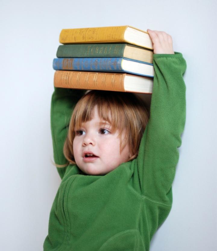 Ein kleines Kind hält einen Stapel aus vier Büchern auf seinem Kopf und wirkt damit größer.
