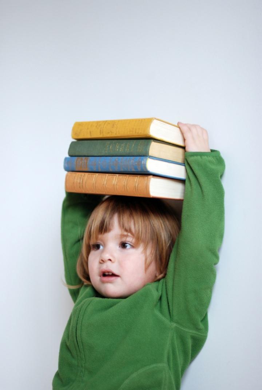 Ein kleines Kind hält einen Stapel aus vier Büchern auf seinem Kopf und wirkt damit größer. (c) luxus/photocase.de