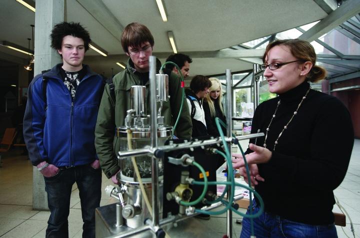 Masterstudentin mit technischem Forschungsaufbau. Studieninteressierte betrachten die Präsentation. (c)