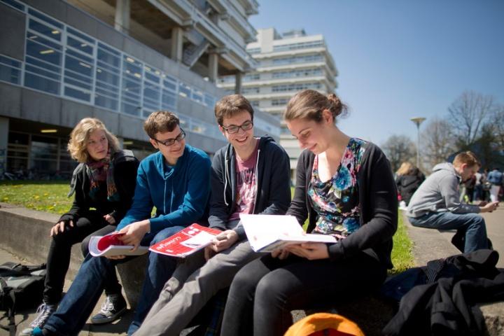 Studierende sitzen auf einer Mauer und lesen in einer Broschüre. (c)