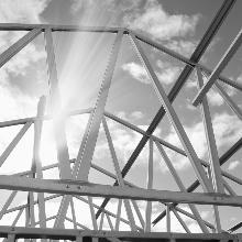 Die Sonne scheint hinter dem Gerüst einer Dachkonstruktion hervor.
