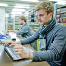 Student in der Bibliothek vor einem Laptop.