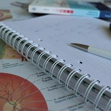 Bachelor Medizintechnik Ein Medizin-Lehrbuch, ein Block und Stift, ein Taschenrechner und ein Anatomie-Poster