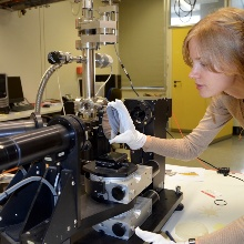 Eine Studentin justiert ein optisches Messgerät.