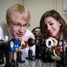 Ein Student stellt ein physikalisches Experiment vor. Im Hintergrund eine Tafel mit Formeln.