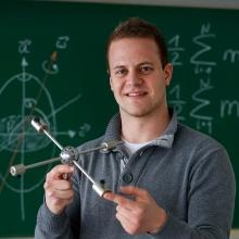 Ein Student stellt ein physikalisches Experiment vor. Im Hintergrund stehen Formeln an einer Tafel.