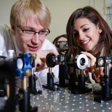 Studierende experimentieren mit kleinen Spiegeln und einem Lichtimpuls.