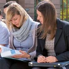 Zwei Studentinnen mit Buch und Notebook