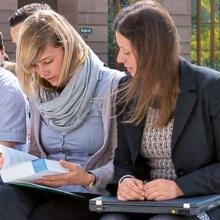 Zwei Studentinnen mit Buch und Notebook. Foto: