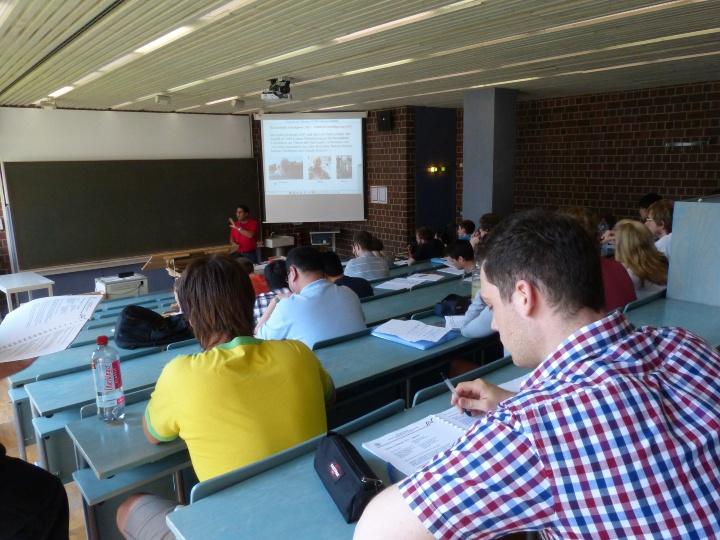 Studierende sitzen in einem Seminar. Die Aufnahme ist in Blickrichtung zur Tafel. (c)