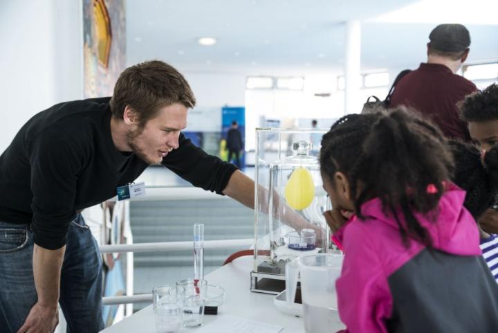 Ein junger Wissenschaftler erklärt Kindern ein Experiment mit einem Luftballon.