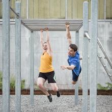Eine Sportlerin und ein Sportler hangeln sich an einem Klettergerüst entlang.