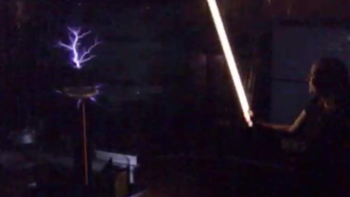 Teslaspule und Leuchtstoffröhre leuchten im Dunkeln.