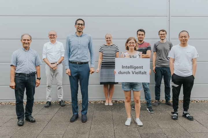 """Eight people of different age, size, gender and origin. In the middle, a sign is held up with the inscription """"Diversity promotes intelligence""""."""